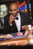 Homem que joga na tabela da roleta no casino fotos de stock