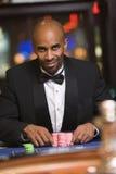 Homem que joga no casino na tabela da roleta imagens de stock