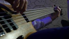 Homem que joga o concerto de rocha da guitarra-baixo closeup vídeos de arquivo