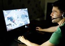 Homem que joga o jogo de vídeo na sala escura Imagens de Stock