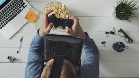 Homem que joga o jogo de vídeo que veste auriculares de VR vídeos de arquivo