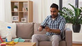 Homem que joga o jogo no smartphone ap?s ter limpado a casa video estoque