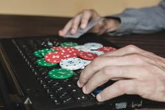 Homem que joga o pôquer em linha com um portátil preto fotos de stock