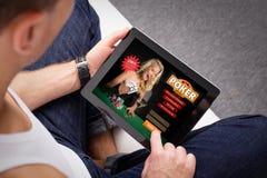 Homem que joga o pôquer na tabuleta fotografia de stock