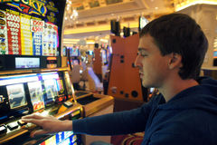Homem que joga o slot machine Imagens de Stock Royalty Free