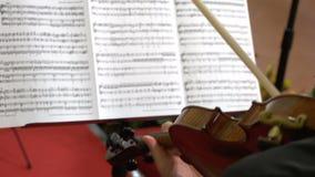 Homem que joga o violino e que olha a partitura video estoque