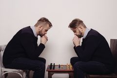Homem que joga a xadrez contra si mesmo fotografia de stock