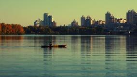 Homem que kayaking na baía na arquitetura da cidade