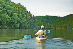Homem que Kayaking no lago quieto Fotos de Stock Royalty Free