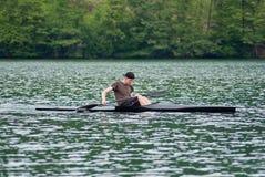 Homem que kayaking no rio da inundação Imagens de Stock