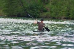 Homem que kayaking no rio da inundação Fotografia de Stock