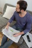 Homem que lê o jornal em um sofá Imagem de Stock Royalty Free