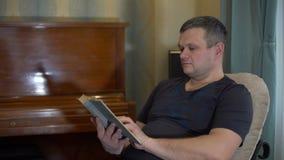 Homem que lê o livro no Appartement vídeos de arquivo
