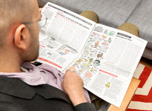 Homem que lê pioliticians de Charlie Hebdo como cogumelos Imagens de Stock