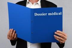 Homem que lê um arquivo médico redigido em francês foto de stock royalty free