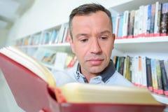 Homem que lê um livro Imagens de Stock