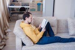 Homem que lê um livro no sofá Imagens de Stock