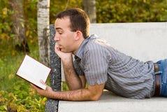 Homem que lê uma novela fotos de stock royalty free