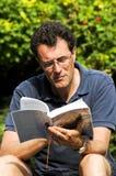 Homem que lê uma novela Fotografia de Stock