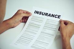 Homem que lê os termos de um seguro Fotos de Stock Royalty Free