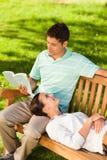 Homem que lê um livro com sua amiga Imagem de Stock