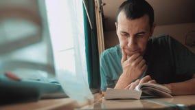 Homem que l? um livro em uma viagem longa do trem Viagem de trem do treinador do conceito do curso da estrada de ferro vista boni video estoque