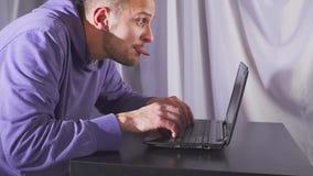 Homem que lambe o portátil video estoque