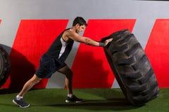 Homem que lança um exercício do gym do exercício do pneu do trator Fotos de Stock Royalty Free