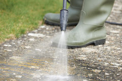 Homem que lava o trajeto concreto com arruela da pressão Foto de Stock Royalty Free