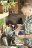 Homem que lava pratos sujos na banca da cozinha Fotografia de Stock