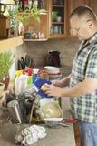 Homem que lava pratos sujos na banca da cozinha Fotos de Stock Royalty Free