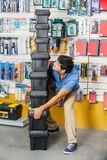 Homem que leva caixas de ferramentas pesadas empilhadas na loja Fotos de Stock Royalty Free