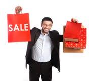 Homem que leva sacos de compras vermelhos da venda imagem de stock