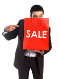 Homem que leva um saco de compras vermelho da venda fotografia de stock royalty free