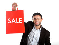 Homem que leva um saco de compras vermelho da venda fotografia de stock