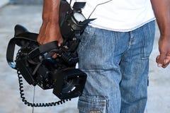 Homem que leva uma câmara de vídeo Fotos de Stock
