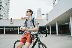 Homem que levanta ao lado de sua bicicleta fotos de stock