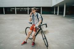 Homem que levanta ao lado de sua bicicleta imagens de stock