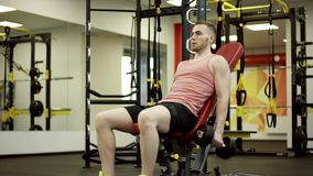 Homem que levanta os pesos e que trabalha seu bíceps no gym vídeos de arquivo
