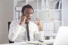 Homem que levanta a voz no telefone imagem de stock