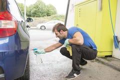 Homem que limpa um carro imagens de stock