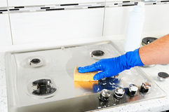 Homem que limpa um fogão de gás Luvas da proteção da mão ao limpar a cozinha Limpeza do close up do fogão de gás foto de stock royalty free