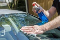Homem que limpa um para-brisa do carro Fotos de Stock Royalty Free