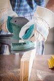 Homem que lixa uma madeira com máquina de lixar orbital Foto de Stock Royalty Free