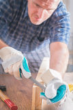 Homem que lixa uma madeira em uma oficina Imagem de Stock