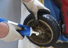 Homem que lubrifica a roda de cortador de grama Fotografia de Stock Royalty Free