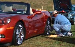 Homem que lustra as rodas de Corveta durante uma feira automóvel Imagens de Stock Royalty Free