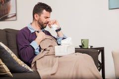 Homem que luta um frio em casa Imagens de Stock Royalty Free