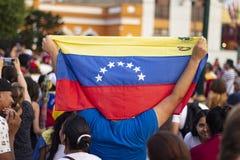 Homem que mantém a bandeira venezuelana no protesto contra Nicolas Maduro fotografia de stock