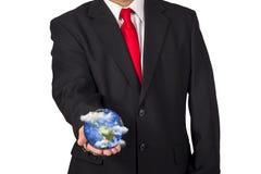 Homem que mantém a terra do planeta disponivel com nuvens de flutuação fotografia de stock